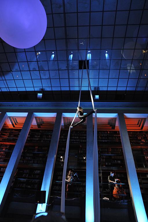 Akrobatartist fra taket i hovedsalen på Deichman Hovedbiblioteket, akkopagnert av to musikere.