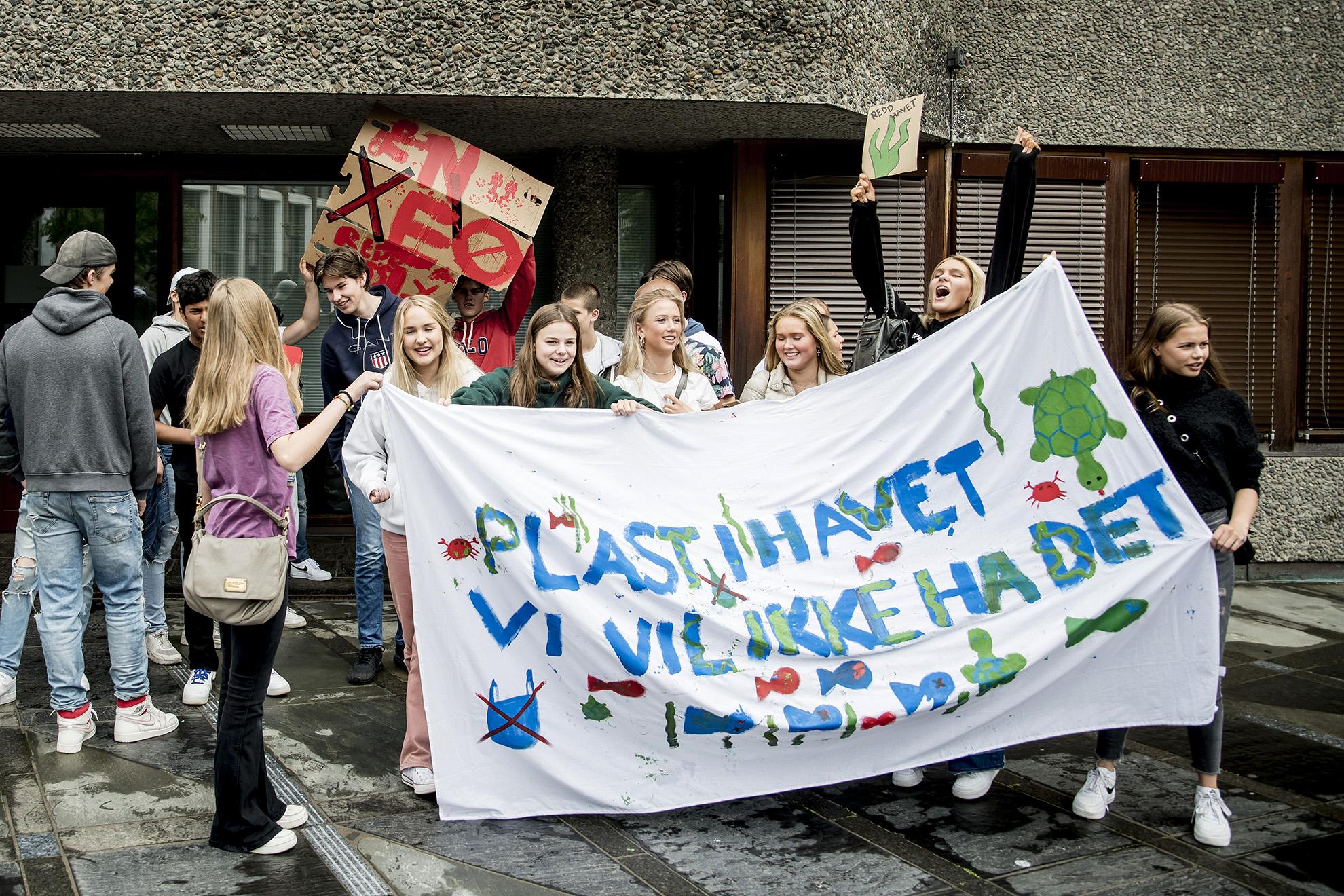 """Ungdom med stort banner med påmalt tekst: """"Plast i havet, vi vil ikke ha det"""""""